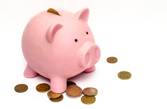 Piggy bank overflowing with coins that have been saved on energy