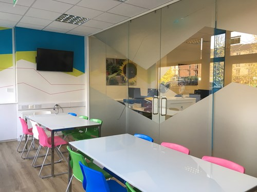View from inside a break room with tables and chairs beside glass partitions for office