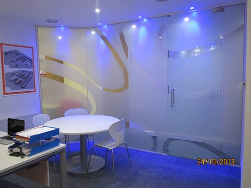 Inside a small office with blue glass partitions for office wrapped around.